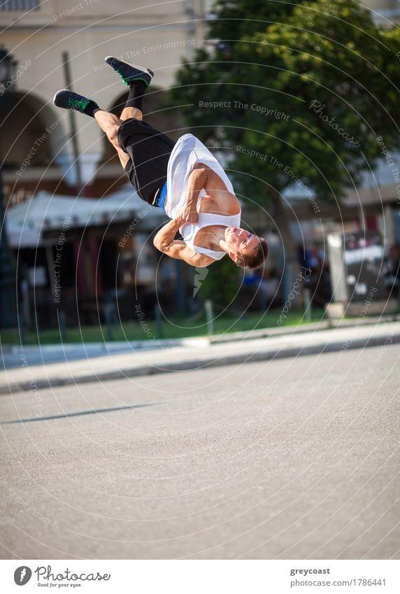Junger Sportler, der seine akrobatischen Fähigkeiten bei einem Salto vorführt. Show in der Stadt Straße Lifestyle Sommer Mensch Mann Erwachsene Bewegung