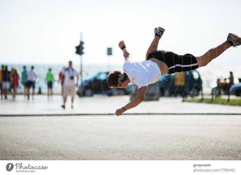Junger sportlicher Mann führt Akrobatik auf einem Stadtplatz auf. Bewegung Schuss während tumbleset in der Luft Lifestyle Sommer Sport Mensch Erwachsene Straße
