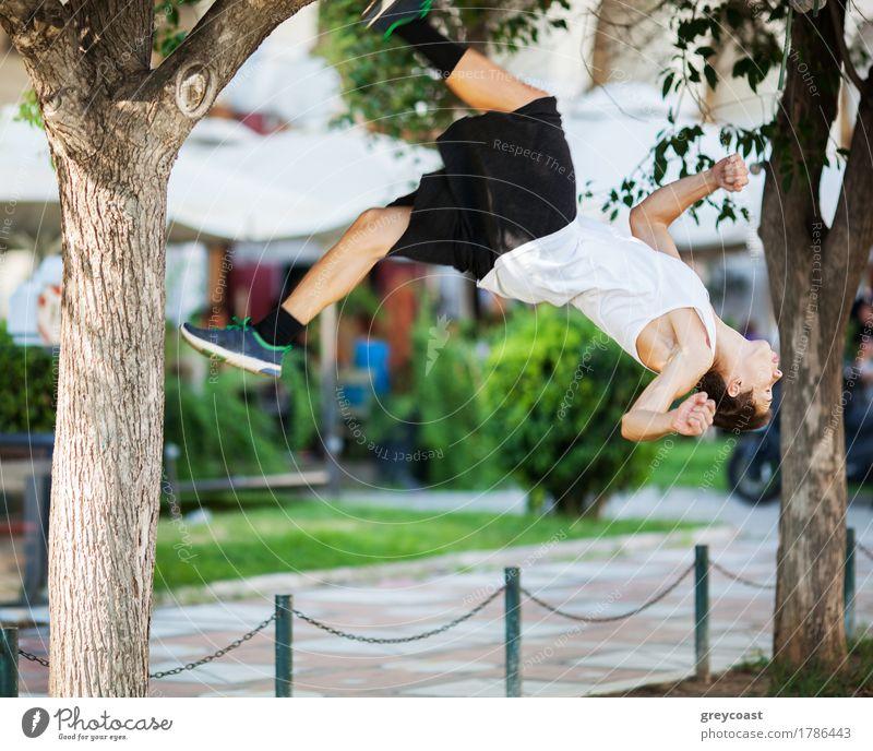 Bewegungsaufnahme eines jungen Sportlers, der in der Stadt Akrobatik betreibt. Frontflip-Trick Lifestyle Sommer Mensch Mann Erwachsene Baum Straße springen frei
