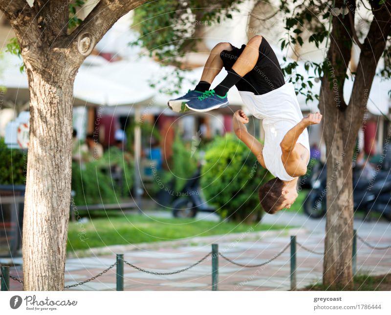 Junge Extremsportler tun Frontflip zwischen den Bäumen. Stadt Straße mit Outdoor-Café im Hintergrund Lifestyle Freiheit Sommer Sport Mensch Mann Erwachsene Baum