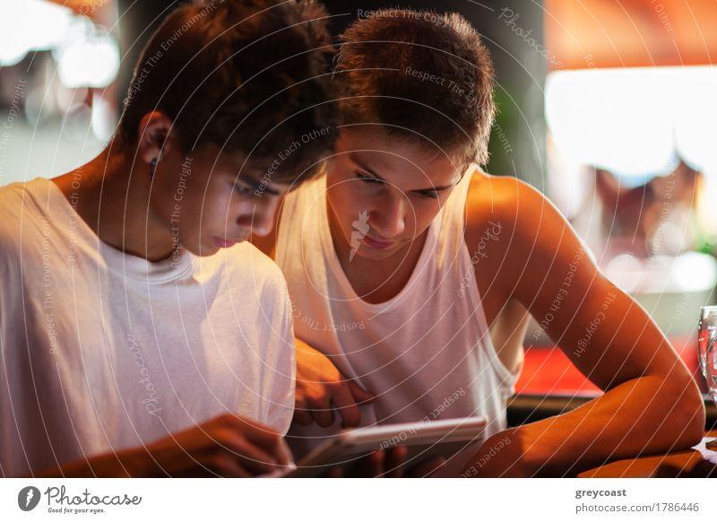Zwei männliche Teenager beim Surfen im Internet in einem Cafe. Unterhalten sich mit Elektronik Freizeit & Hobby Computer Mensch Mann Erwachsene Freundschaft