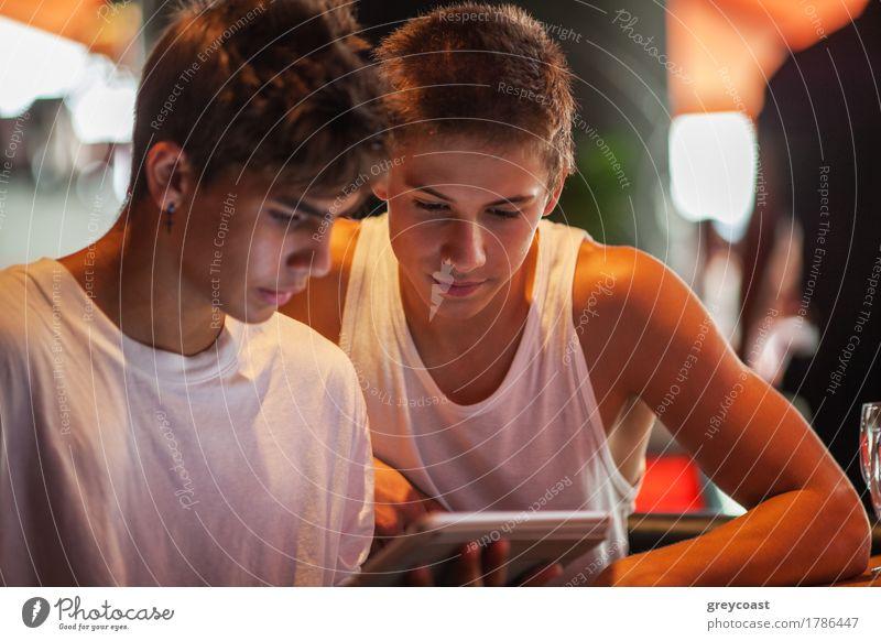 Zwei Teenager in weißen Sport-Shirts mit Tablet-PC in der Cafeteria. Sie schauen auf den Pad-Bildschirm Freizeit & Hobby Entertainment Computer Internet Mensch