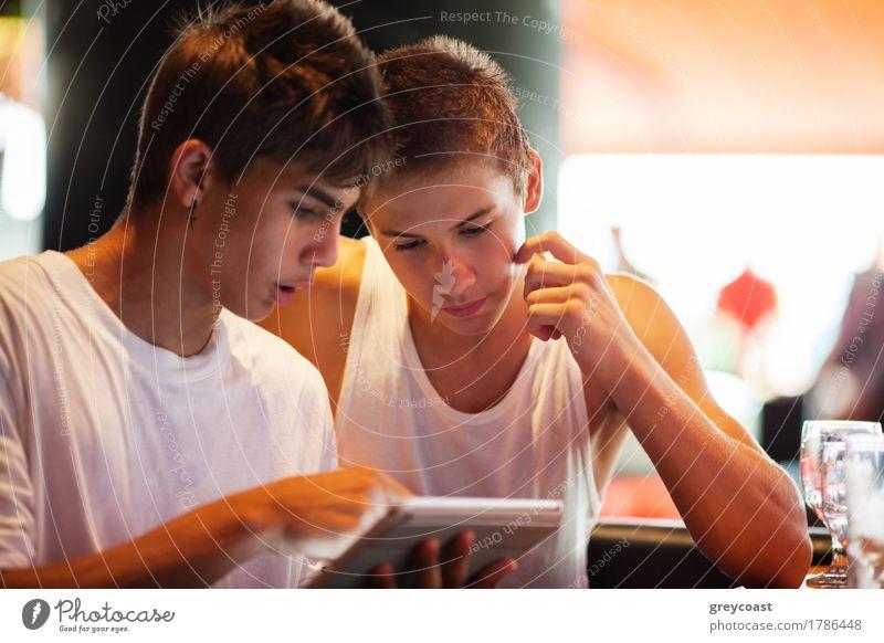 Zwei männliche Teenager surfen im Internet auf einem Tablet-Computer, während sie in einem Café sitzen. Ein junger Mann, der auf den Bildschirm zeigt