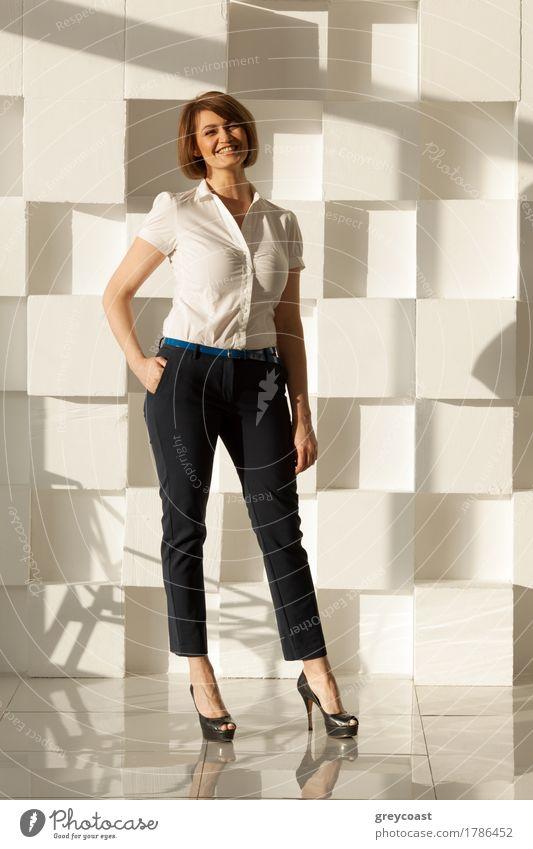 Lächelnde Geschäftsfrau in Stöckelschuhen schaut in die Kamera, während sie die Hand in der Tasche hält. Moderne weiße Wand auf dem Hintergrund Lifestyle