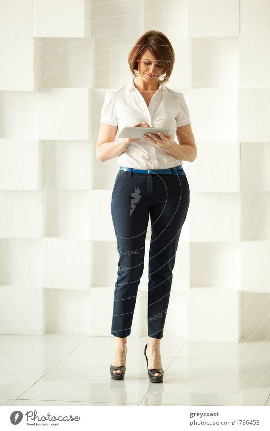 Lächelnde Geschäftsfrau, die gegen eine weiße Wand steht und auf ein Tablet in ihrer Hand schaut Lifestyle elegant Stil Büro Business Erwachsene Urelemente