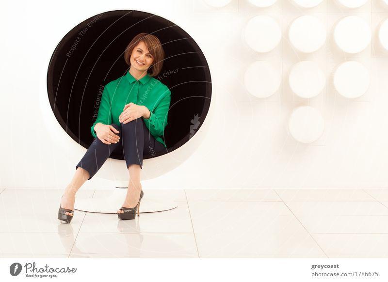 Attraktive erwachsene Frau sitzt auf kugelförmigen Stuhl mit Händen auf den Knien. Moderne weiße Wand auf dem Hintergrund Lifestyle elegant Stil Büro Mensch