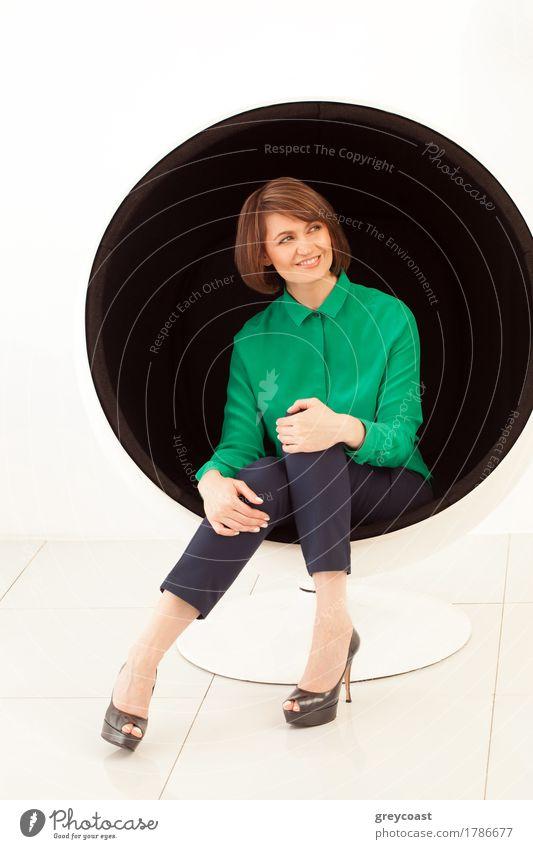 Nahaufnahme einer rothaarigen lächelnden Frau in eleganter Kleidung, die wegschaut, während sie auf einem modernen Stuhl sitzt. Weißer Hintergrund Lifestyle