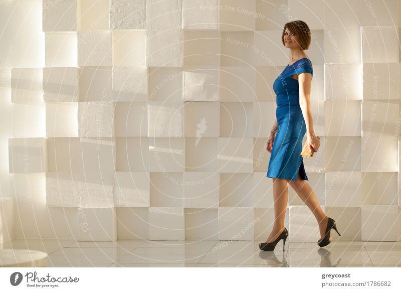 Lächelnde Frau in eleganten blauen Kleid zu Fuß gegen moderne Wand mit Brieftasche in der Hand, während der Blick auf die Kamera Lifestyle Stil Büro Mensch