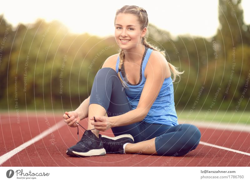 Sportliche junge Frau, die ihre Spitzee bindet Mensch Jugendliche Sommer schön Sonne 18-30 Jahre Erwachsene Wärme Lifestyle Textfreiraum Aktion blond Schuhe