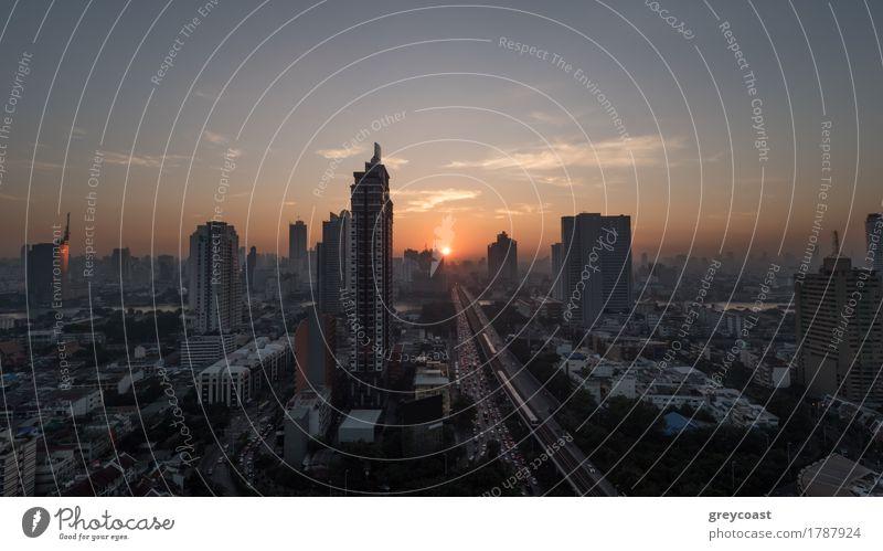 Sonnenuntergang Zeit in Bangkok, Thailand. Stadtpanorama mit Hochhaus städtische Architektur und Verkehr auf der Autobahn. Himmel in warmen Farben und Sonne untergehen