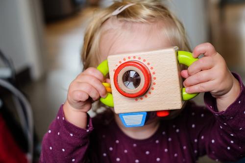 Mädchen mit Spielzeug Kamera Fotokamera feminin Kind 1 Mensch 1-3 Jahre Kleinkind beobachten warten blond Coolness einfach frisch lustig braun Vorfreude