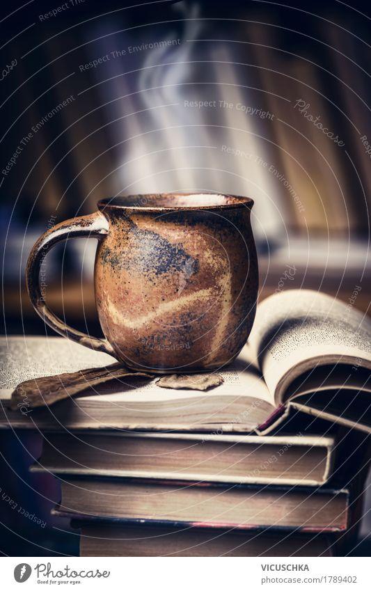 Tasse mit heißem Getränk auf Bücher Stapel dunkel Lifestyle Stil Design Häusliches Leben retro Tisch lernen Buch lesen Kaffee Bildung Tee altehrwürdig