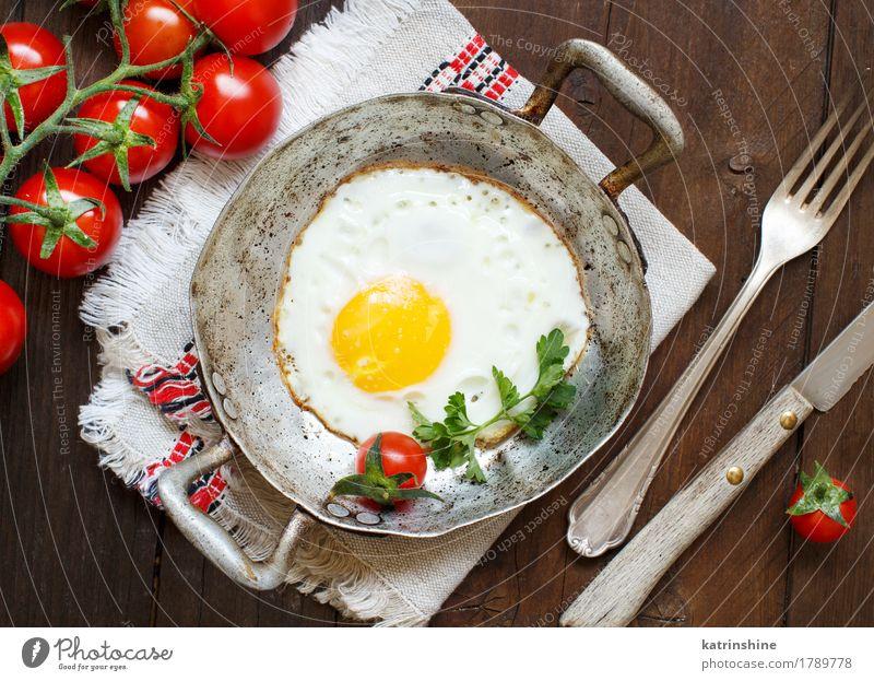 Spiegelei mit Tomaten und Kräutern Gemüse Essen Frühstück Abendessen Pfanne Tisch Holz frisch gelb grün rot Cholesterin Eierschale braten Mahlzeit Protein