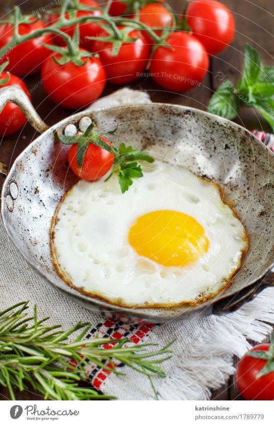 Spiegelei mit Tomaten und Kräutern Gemüse Essen Frühstück Abendessen Pfanne Tisch Holz frisch gelb grün rot Cholesterin braten Mahlzeit Protein rustikal