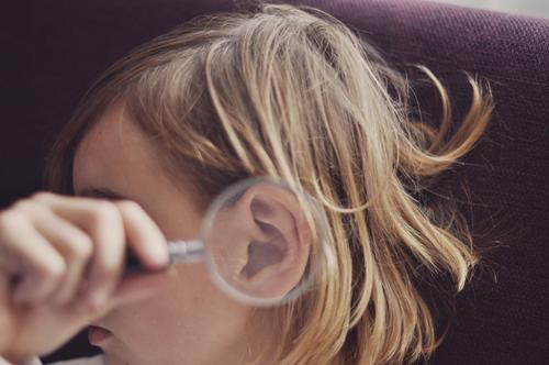 besser hören   jugentlich mit einer lupe am ohr Kopf Mensch Kind Mädchen Jugendliche Junge Frau Hand Lupe Ohr vergrößert Ohrmuschel Gehörsinn akustisch