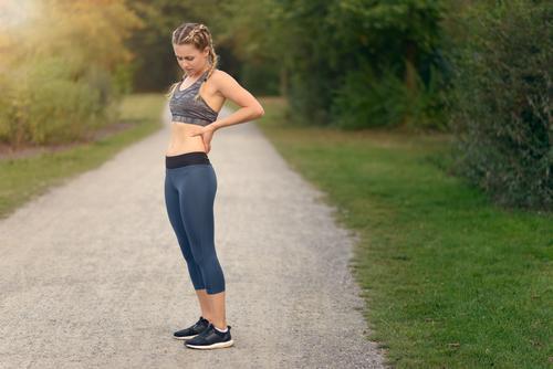 Sportlerin mit Schmerz in ihr zurück beim Laufen Mensch Frau Jugendliche Pflanze Sommer grün Hand Landschaft Blatt 18-30 Jahre Gesicht Erwachsene Textfreiraum
