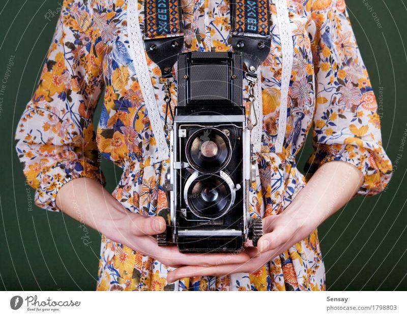 Weinlesekamera in der Hand auf Grün Stil schön Fotokamera Mensch Mädchen Frau Erwachsene Blume Mode Kleid alt retro grün rot weiß Farbe altehrwürdig Fotografie
