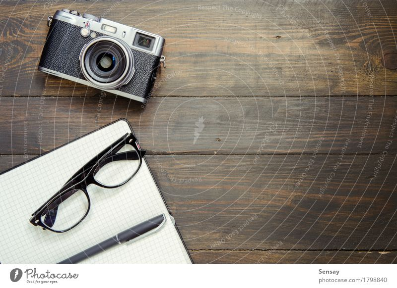 Kamera, Brille und Notizblock auf Holz alt Stil Business oben Design Textfreiraum Büro retro Aussicht Tisch Papier Fotokamera Schreibtisch Schreibstift Top
