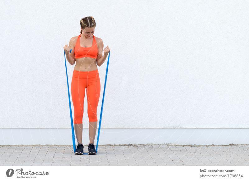 Junge sportliche Frau, die Übungen mit einer Latexband tut Mensch Jugendliche 18-30 Jahre Erwachsene Lifestyle Sport Glück Körper blond Lächeln Fitness Band