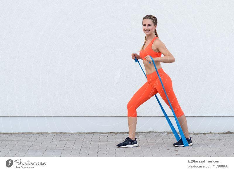 Junge sportliche Frau, die Übungen mit einer Latexband tut Lifestyle Glück Körper Sport Erwachsene 1 Mensch 18-30 Jahre Jugendliche Band blond Fitness Lächeln