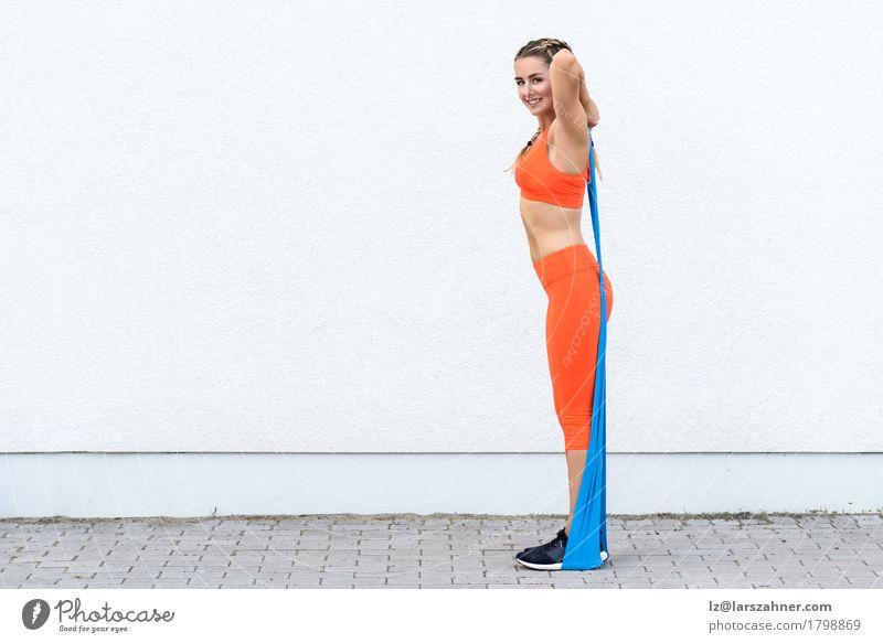Junge sportliche Frau, die Übungen mit einer Latexband tut Mensch Jugendliche 18-30 Jahre Erwachsene Lifestyle Sport feminin Glück Körper blond Lächeln Fitness