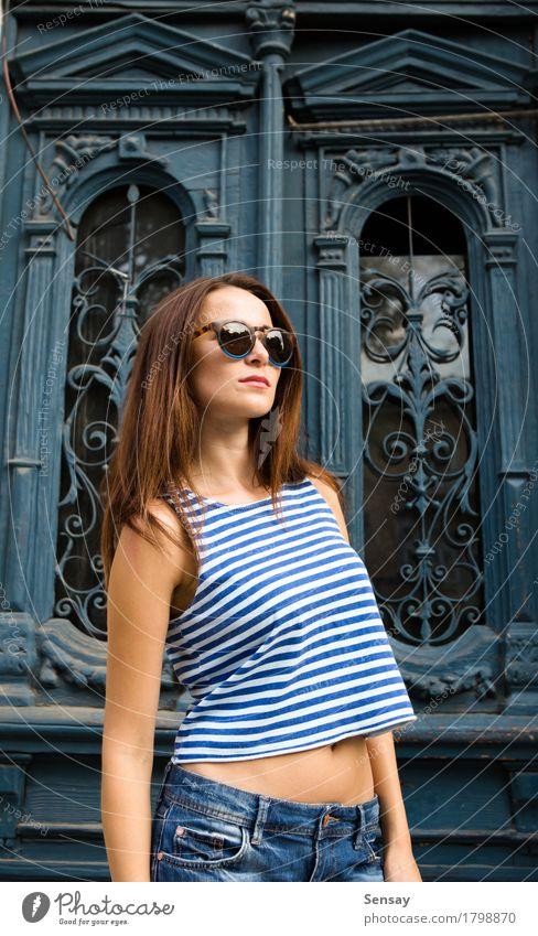Mädchen, das auf dem alten Türhintergrund steht Stil Glück schön Sonne Mensch Frau Erwachsene Band Mode Hemd Jeanshose Sonnenbrille Holz Streifen stehen trendy