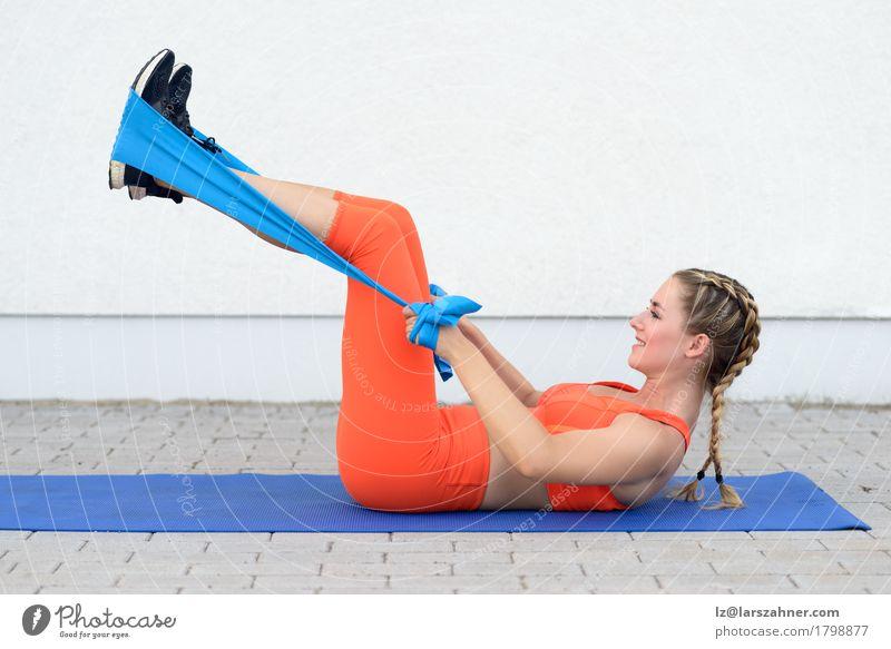 Junge sportliche Frau, die Übungen mit einer Latexband tut Lifestyle Glück Körper Sport feminin Erwachsene 1 Mensch 18-30 Jahre Jugendliche Band blond Fitness