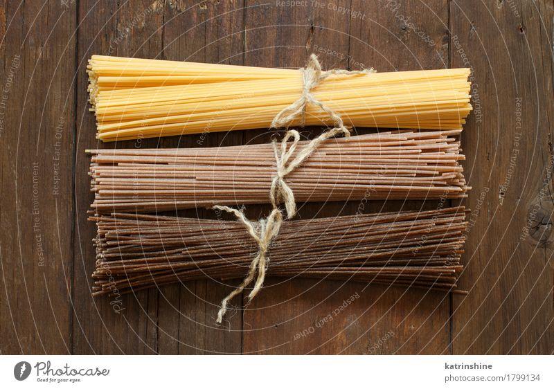 Italienische Spaghettis auf dem alten Holztisch Teigwaren Backwaren Ernährung Tisch braun Hintergrund Holzplatte Land Essen zubereiten kulinarisch Lebensmittel
