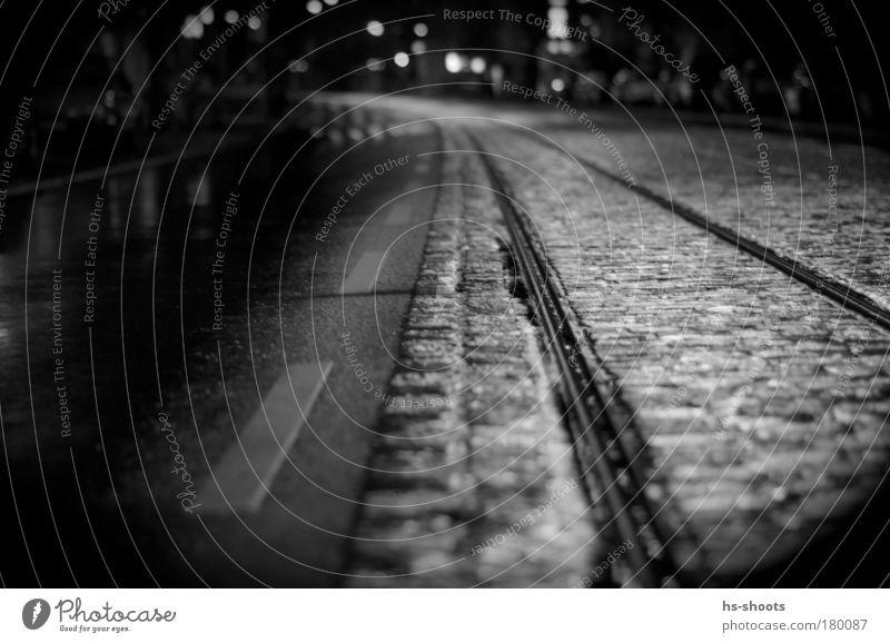 Bahngleise und Straße Stadt Einsamkeit Straße Regen Nacht Deutschland Verkehr Gleise Verkehrswege Erwartung Straßenbahn S-Bahn Verkehrsmittel Freiburg im Breisgau Schwarzweißfoto Bahnfahren