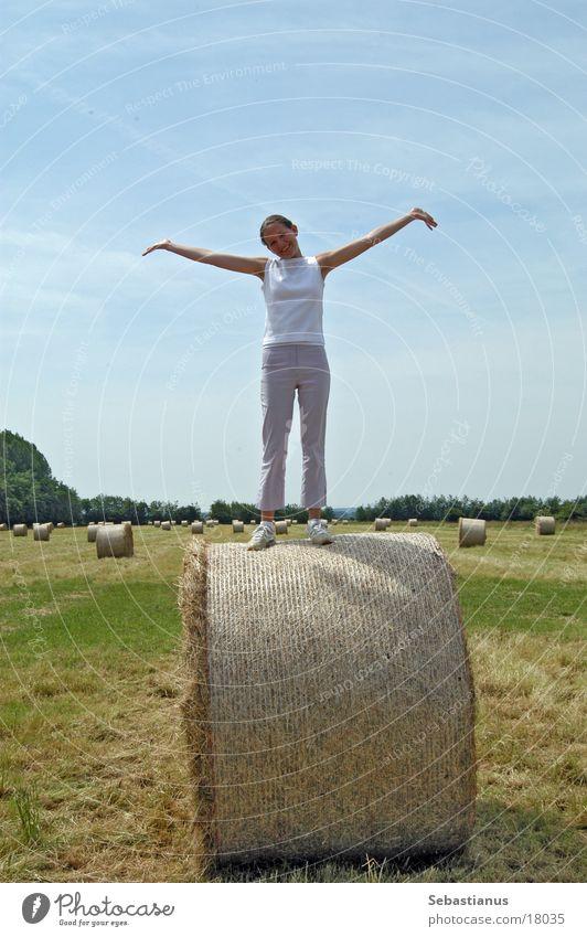 Ein Knuffelchen auf dem Strohlballen Frau Sommer Wiese Glück Feld Arme Fröhlichkeit 18-30 Jahre Ernte Lebensfreude positiv Junge Frau sommerlich Strohballen