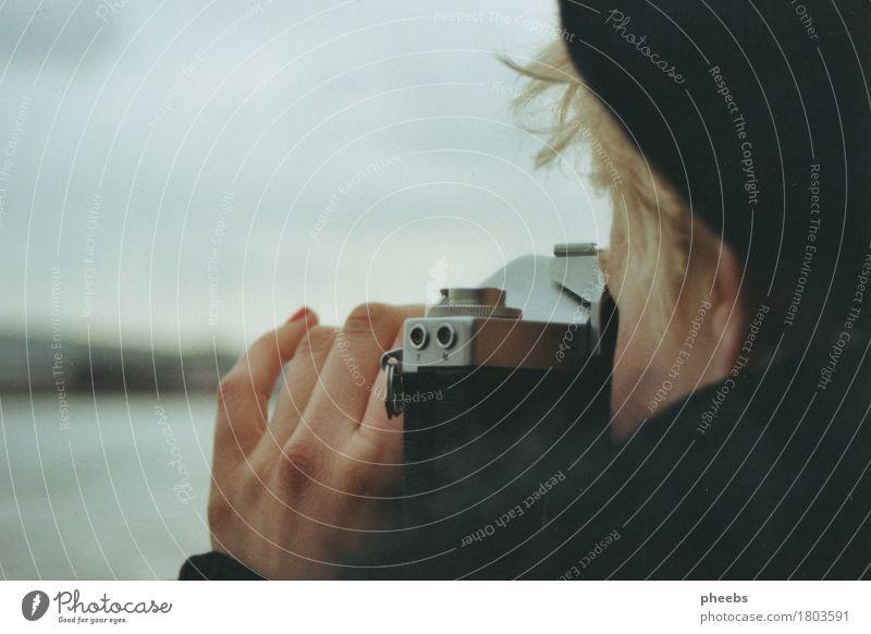 weitblick Frau Mädchen Hand Fotokamera analog Meer See Fluss Mütze Winter grau Schulter Finger Haare & Frisuren blond