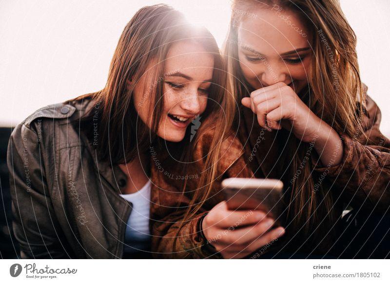 Glückliche Jugendlichmädchen, die das intelligente Telefon betrachtet Bilder verwenden Lifestyle Technik & Technologie Unterhaltungselektronik Telekommunikation
