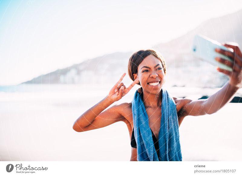 Afrikanische junge Frau, die lustiges selfie mit Smartphone nimmt Mensch Jugendliche Junge Frau Meer Freude Strand 18-30 Jahre Erwachsene Sport Glück Felsen