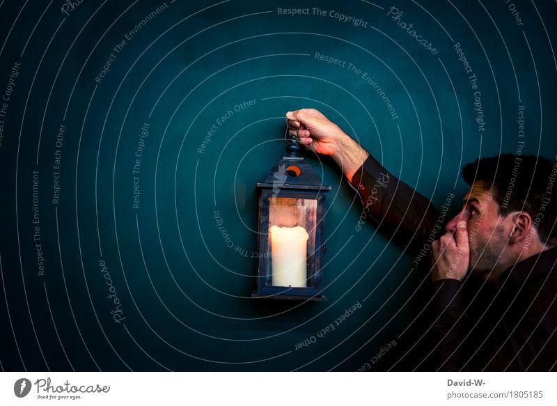 Mann hält eine Laterne ins dunkle und erschrickt als er plötzlich ... Kerze Entdeckung angst sehen Spannung erschrocken Angst Licht Farbfoto dunkel Mensch