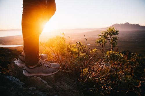 Nahaufnahme des stilvollen Turnschuhs in der Natur Abenteuer Sommer Sonne Berge u. Gebirge wandern Sport Fuß Landschaft Wärme Mode Schuhe Fitness stehen gold