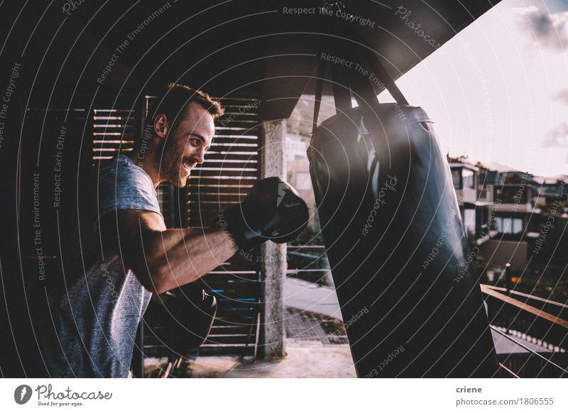 Junger erwachsener Mann, der zu Hause boxendes Training auf seinem Balkon tut Mensch Jugendliche 18-30 Jahre Erwachsene Lifestyle Sport modern Lächeln Fitness