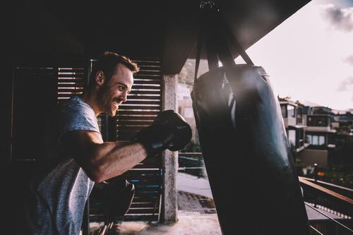 Junger erwachsener Mann, der zu Hause boxendes Training auf seinem Balkon tut Lifestyle Körperpflege Sport Fitness Sport-Training Mensch Erwachsene Jugendliche