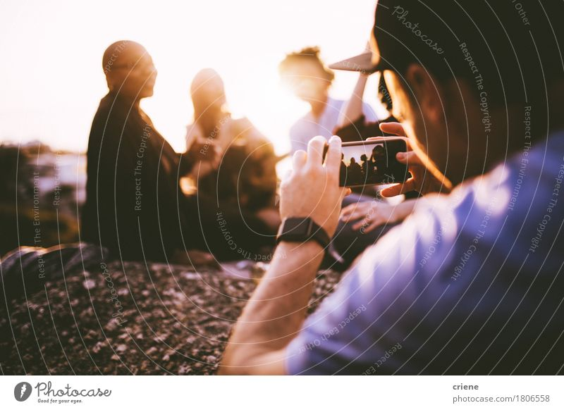 Junger erwachsener Mann, der Foto mit intelligentem Telefon seiner Freunde macht Lifestyle Freude Sommer Sonne Party ausgehen Feste & Feiern Fotokamera
