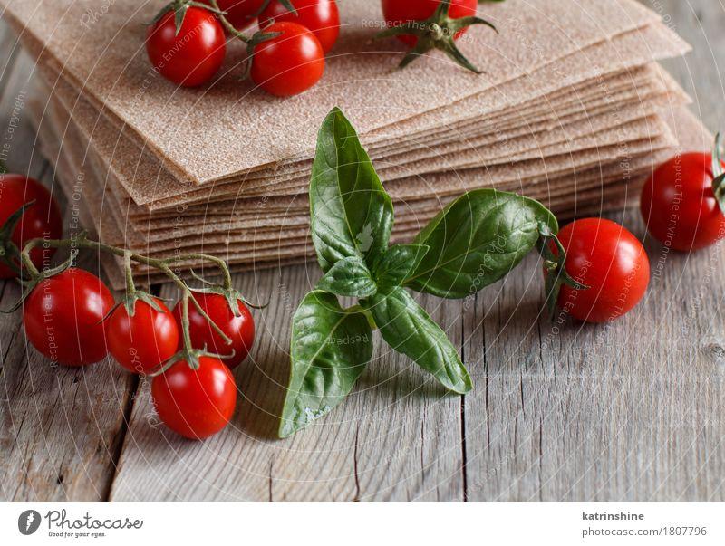 Rohe Lasagne Blätter und Kirschtomaten Gemüse Teigwaren Backwaren Ernährung Italienische Küche Tisch alt braun rot Tradition Essen zubereiten kulinarisch