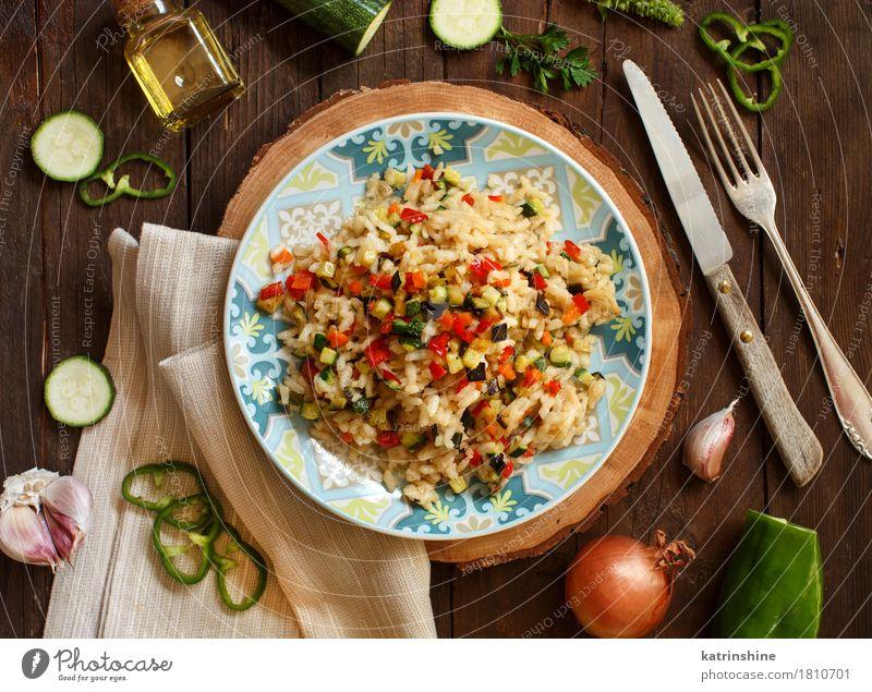 Risotto mit Gemüse Getreide Öl Ernährung Mittagessen Abendessen Vegetarische Ernährung Diät Italienische Küche Teller Flasche Gabel Holz lecker Koch