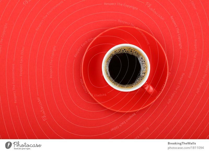 Schwarzer Kaffee in der roten Schale mit Untertasse auf rotem Papier, Draufsicht Frühstück Kaffeetrinken Getränk Heißgetränk Becher genießen Aggression stark