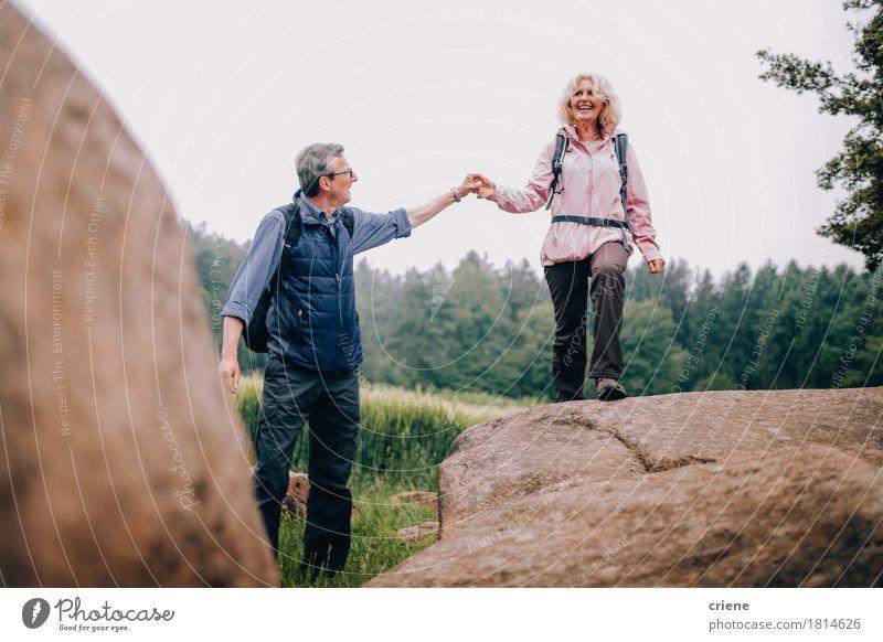 Älterer Mann, der seiner Frau einen Felsen auf Wanderung oben klettern hilft Ferien & Urlaub & Reisen Erholung Freude Erwachsene Senior Sport Lifestyle Paar