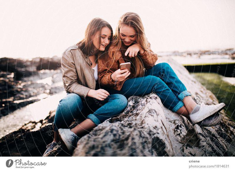 Glückliche junge Jugendlichmädchen, die intelligentes Telefon betrachten Mensch Frau Jugendliche Junge Frau Meer Freude Mädchen Strand Erwachsene Gefühle