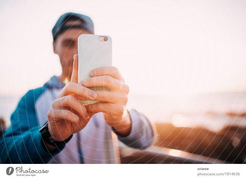 Junger erwachsener Mann, der Foto mit dem intelligenten Telefon im Freien macht Mensch Jugendliche Hand Junger Mann Meer Strand 18-30 Jahre Erwachsene Lifestyle