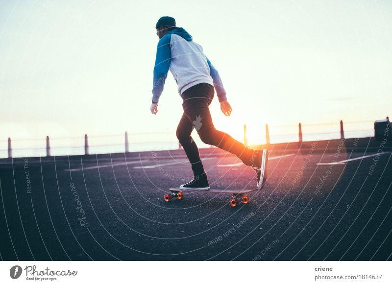 Hippie-Junge, der mit langem Brett auf Promenade im Sonnenuntergang rollt Mensch Jugendliche Mann Junger Mann Erholung Erwachsene Straße Sport Lifestyle