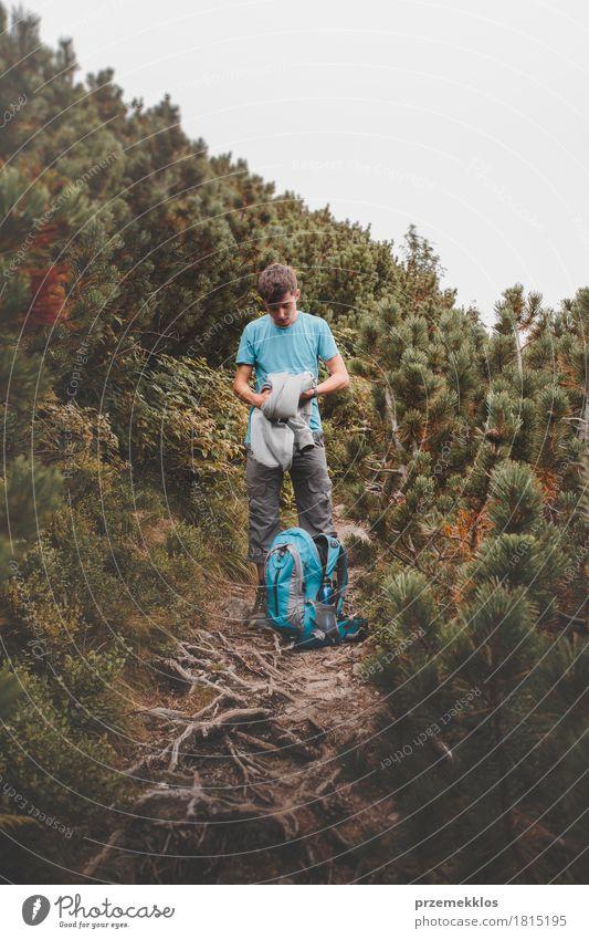 Junge, der seine Kleidung zum Rucksack auf Spur verpackt Lifestyle Ferien & Urlaub & Reisen Abenteuer Freiheit Sommer Berge u. Gebirge wandern 1 Mensch Natur