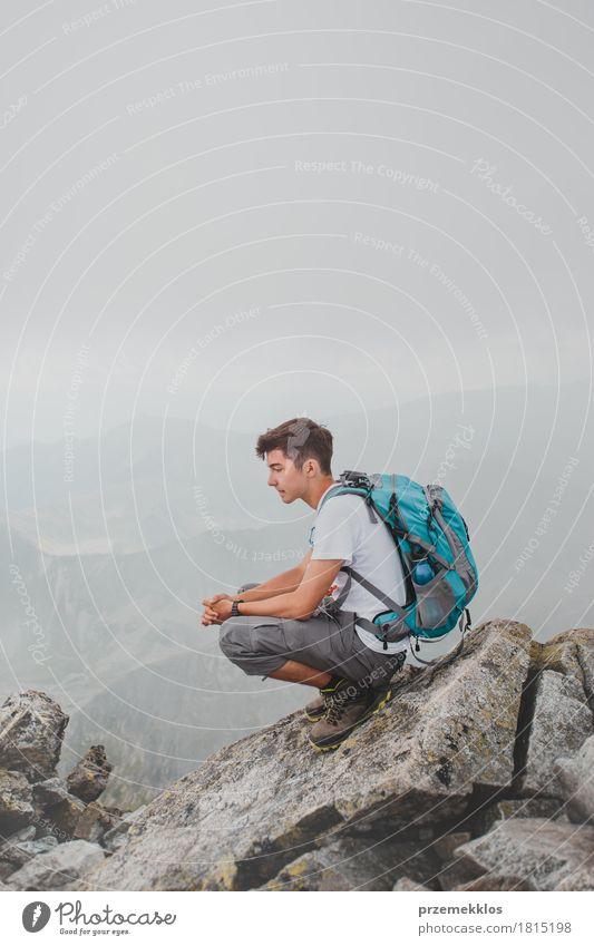 Junge, der auf einer Bergspitze sitzt Ferien & Urlaub & Reisen Abenteuer Freiheit Sommer Sommerurlaub Berge u. Gebirge wandern 1 Mensch 13-18 Jahre Jugendliche