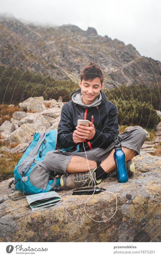 Junge, der auf einem Felsen stillsteht und einen Handy auflädt Mensch Natur Ferien & Urlaub & Reisen Jugendliche Sommer Erholung Einsamkeit Berge u. Gebirge
