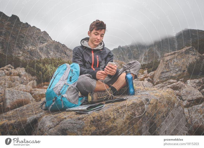 Junge, der auf einem Felsen stillsteht und einen Handy auflädt Flasche Lifestyle Freizeit & Hobby Ferien & Urlaub & Reisen Abenteuer Freiheit Sommer