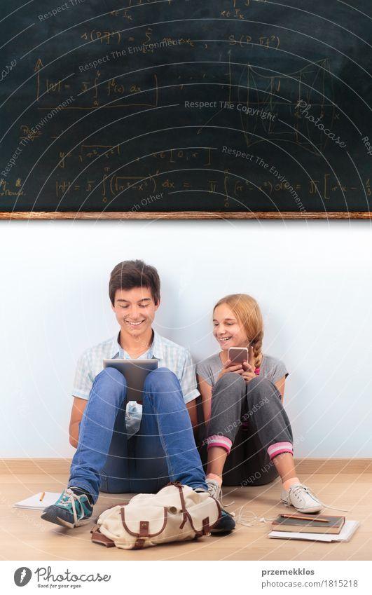 Jugendliche, die in der Schule durch eine Tafel lernen Mensch Mädchen sprechen Junge Glück Denken 13-18 Jahre Computer Buch Papier Studium Bildung Student